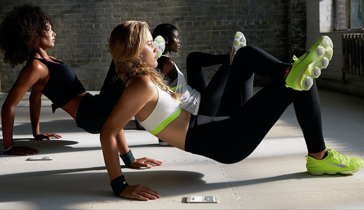 Three women wearing Nike in fitness class crossed legs