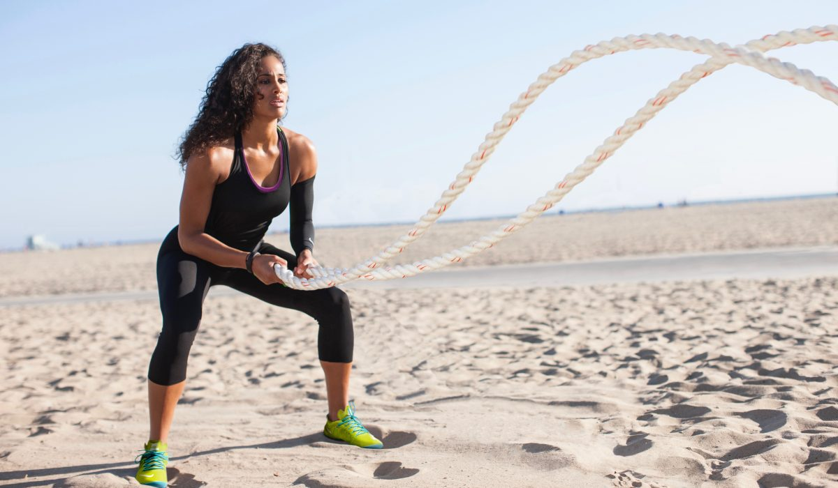 HIIT Workout - rope fitness - woman on the beach working out